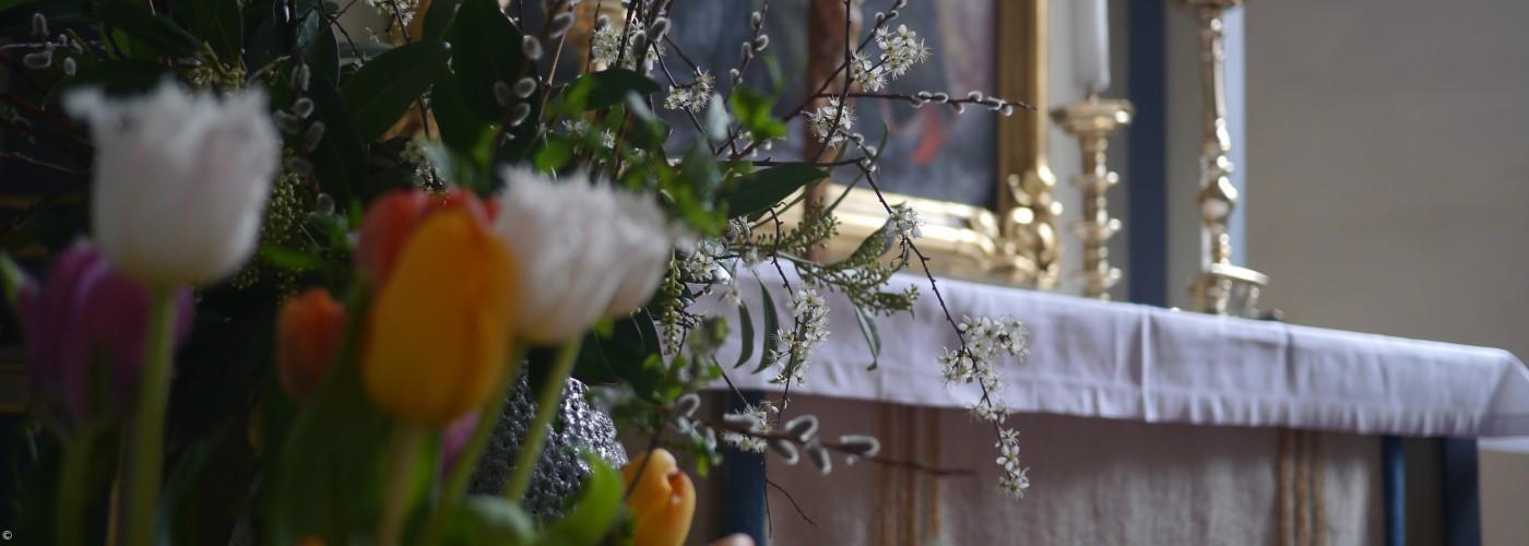 Blick über frühlingshaftes Blumenarrangement auf den Altar von St. Bartholomäus